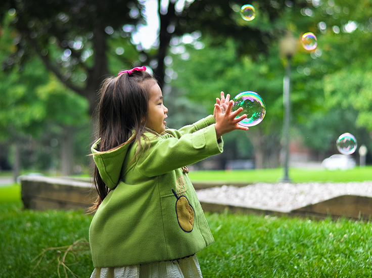 Child in a park with a bubble
