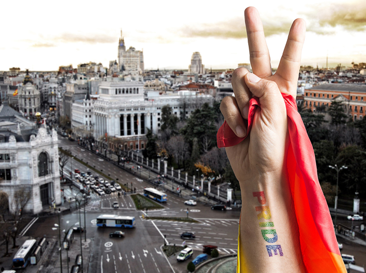 Hand with pride written, making a peace sign over a city