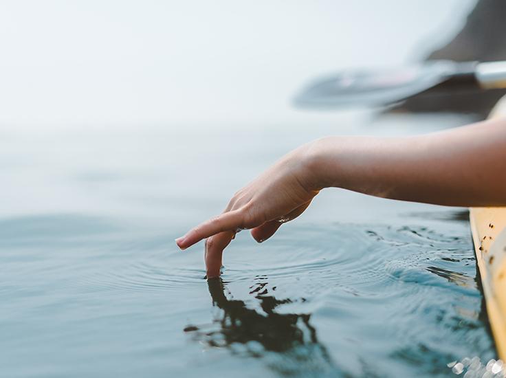 Person running hand through water