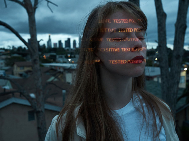 Woman with writing projected onto her face