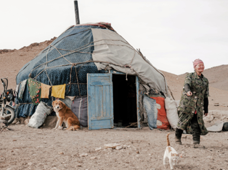 A woman outside her home with a dog and cat