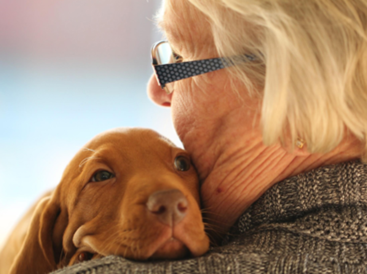 An elderly woman shares a cuddle with her dog