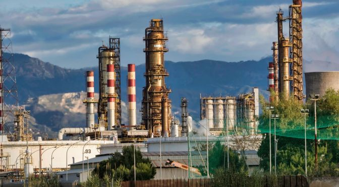 An oil refinery with mountains in the background
