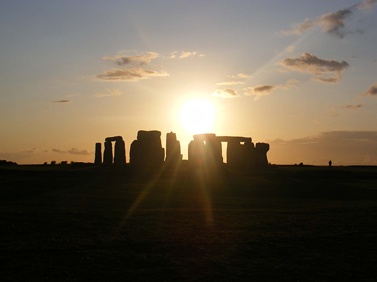 The sun rising behind Stonehenge