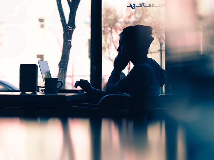 Man on a laptop by a window