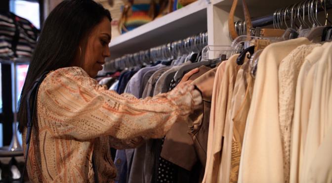 Tania Arrayales looking through a clothes rail