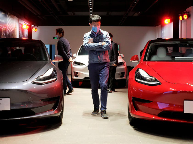 Shoppers in face masks following the coronavirus outbreak view Tesla Model 3 sedans and Tesla Model X sport utility vehicles at a new Tesla showroom in Shanghai, China in May (REUTERS/Yilei Sun) ( REUTERS )