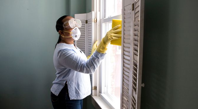Woman cleaning a window with a mask on