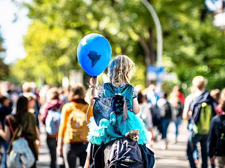 Child at a protest with an earth balloon