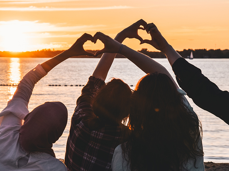 Group of friends in front of the water, making heart symbols with their hands